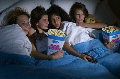 Girls at sleepover watching scary movie